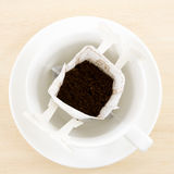 The instant freshly brewed coffee drip bag. On white coffee cup royalty free stock image