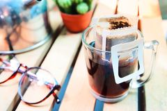 Instant freshly brewed glass of coffee, Drip bag fresh coffee. On wooden table in garden backyard royalty free stock photos