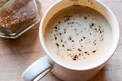 Instant granulated coffee powder with milk in cup Stock Photography