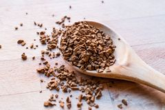 Instant Granulated Coffee Powder on Wooden Spoon. Stock Photo