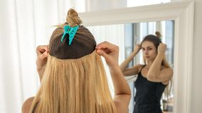 Instant hair extensions on hairpins for volume and elongation. blonde strands. Instant hair extensions on hairpins for volume and elongation. Light blonde stock photography