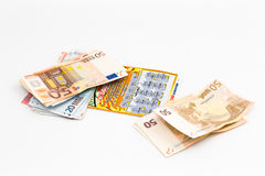 Instant lottery. An instant lottery ticket with a lot of money next Royalty Free Stock Images