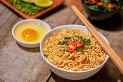 Instant noodle in bowl cooked spicy taste topping with eggs.  royalty free stock photos