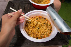 Instant noodle and hand with food sticks Royalty Free Stock Images