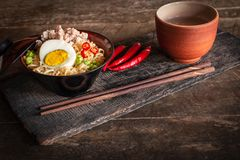 Instant noodle with pork, egg and vegetables on black bowl on the wood table there are chilli, chopstick and drinking glass placed. Around close up royalty free stock image