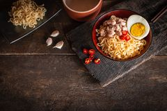 Instant noodle with pork, egg and vegetables on black bowl on the wood table there are chilli, chopstick, garlic, instant noodle. In black plate and drinking stock photo