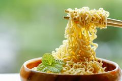 Instant noodle in wooden bowl with bamboo chopstick on green bac Stock Photos