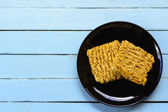 Instant noodles in black dish on blue background. Stock Images