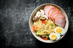 Instant noodles in bowl with broccoli, mushrooms, becon and egg royalty free stock images