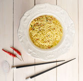 Instant noodles in bowl  with chopsticks. Instant noodles in bowl with chopsticks and red chili pepper on wooden background - top view Stock Photo