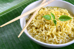Instant noodles. A bowl of delicious intent noodles with a jar of olive oil back stock image