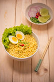 Instant noodles in bowl with vegetables and  boiled egg on wood Stock Photography
