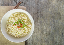 Instant noodles in bowl on wood background. Stock Photography