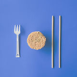 Instant noodles isolated on blue background. Chopsticks Stock Photography