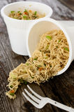 Instant noodles pasta ramen spilled on rustic wood table Royalty Free Stock Images
