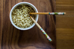 Instant Noodles in a Plastic Bowl with Chopsticks on a wooden surface. Royalty Free Stock Photos