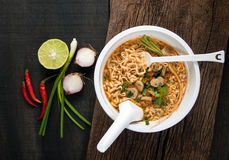 Instant noodles in plastic bowl and vegetable side dishes on woo. D background. Quick & easy food concept royalty free stock photography