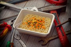 Instant noodles ramen on a wooden table with working tools. Time lapse lunch for construction worker Royalty Free Stock Images