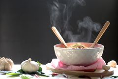 Instant noodles and spoon with wooden fork in cup with smoke ris stock photography