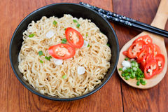 Instant noodles to eat sliced onions and peppers. On wooden table Stock Photos