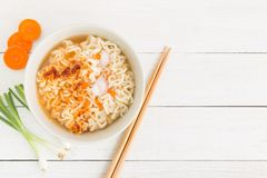 Instant noodles and vegetables on white wooden background, Top view of noodle and seasonings in cup on wood table stock photos