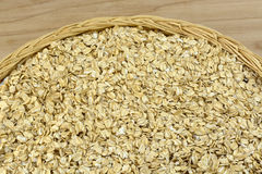 Instant oatmeal. Raw uncooked heap of instant oatmeal cereal ln wicker plate royalty free stock photo
