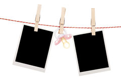 Instant photo frames and pacifier hanging on the clothesline. Isolated on white background Royalty Free Stock Images