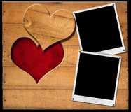 Instant Photo Frames on Wooden Boards. Two instant photo frames on brown wooden wall with a hole in the shape of heart and red velvet background with roses Royalty Free Stock Photography