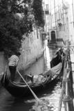 A gondolier intent on rowing on his gondola in a canal in Venice royalty free stock image