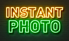 Instant photo neon sign on brick wall background. Royalty Free Stock Photography