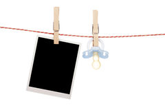 Instant photo and pacifier hanging on the clothesline. Isolated on white background Royalty Free Stock Photos