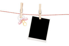 Instant photo and pacifier hanging on the clothesline. Isolated on white background Stock Photo