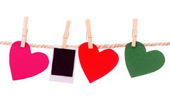 Instant photograph and paper heart shapes hanging Royalty Free Stock Photos