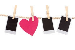 Instant photographs and heart shape hanging on a Royalty Free Stock Images