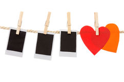 Instant photographs and heart shapes hanging on a Royalty Free Stock Photography