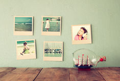 Instant photos hang over wooden textured background next to decorative boat in the bottle. retro filtered image Royalty Free Stock Photos