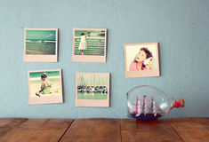 Instant photos hang over wooden textured background next to decorative boat in the bottle. retro filtered image Royalty Free Stock Image