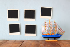 Instant photos hang over wooden textured background next to decorative boat. retro filtered image Stock Image