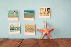 Instant photos hang over wooden textured background next to decorative starfish. retro filtered image Stock Photos