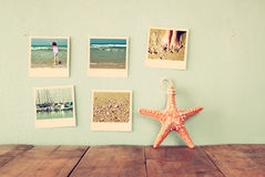 Instant photos hang over wooden textured background next to decorative starfish. retro filtered image Stock Photo