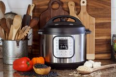 Instant Pot with Beans Rice and Fresh Vegetables. Breeding, KY, USA - January 08, 2019: Instant Pot pressure cooker on kitchen counter with beans and rice stock photos