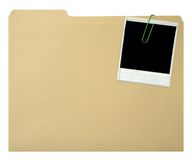 Instant print and file folder. Blank instant print paper-clipped to file folder Royalty Free Stock Image