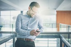Instantly connected to his clients. Business man standing in business building. Business man typing on smart phone royalty free stock images