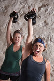 Instense Boot Camp Style Workout. Instense women shout as they push kettle bell weights up Stock Images