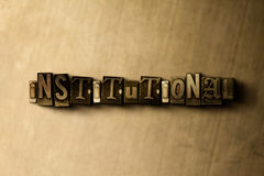 INSTITUTIONAL - close-up of grungy vintage typeset word on metal backdrop Royalty Free Stock Images