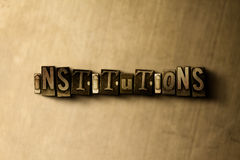 INSTITUTIONS - close-up of grungy vintage typeset word on metal backdrop Stock Photography