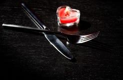 Inställningen för valentindagtabellen med kniven, gaffel, röd brinnande hjärta formade stearinljuset Royaltyfri Bild