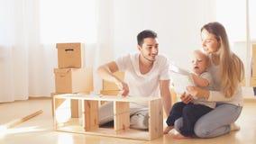 Instrução da leitura da família e para montar junto a mobília na sala de visitas da pilha nova do apartamento de caixas moventes  vídeos de arquivo