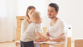 Instrução da leitura da família e para montar junto a mobília na sala de visitas da pilha nova do apartamento de caixas moventes  video estoque