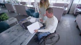 Instrução profissional do homem maduro deficiente na cadeira de rodas com as mulheres do professor que usam a informática esperta vídeos de arquivo